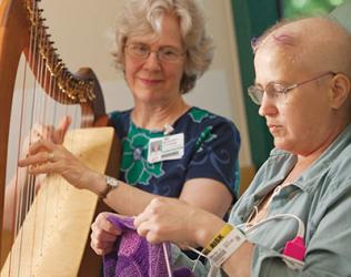 A lady plays the harp as a patient listens.