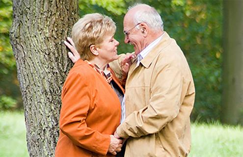 An older couple about to kiss